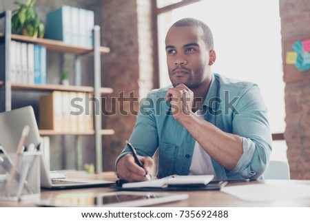 Skeptic, unsure, uncertain, doubts concept. Young african student is making decision sitting at the office in casual smart Royalty-Free Stock Photo #735692488