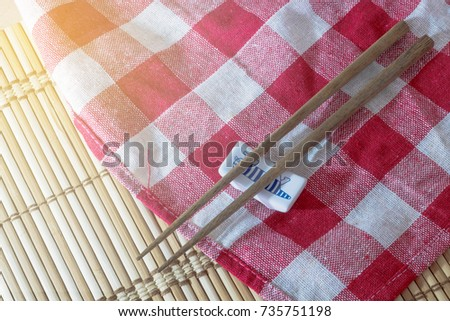 chopsticks put on red and white table cloth placed on a bamboo mat #735751198