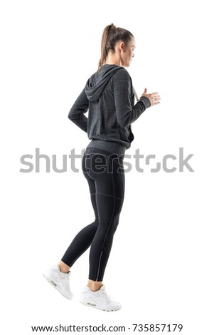 Rear side view of sporty female jogger jogging in hooded sweatshirt and leggings. Full body length portrait isolated on white background.  #735857179
