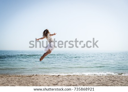 Happy beautiful young girl jumping #735868921