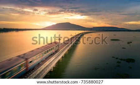 The train was running at high speed through a railway bridge Over Lake Pa Sak Dam Lopburi Thailand Beautiful Sunset #735880027