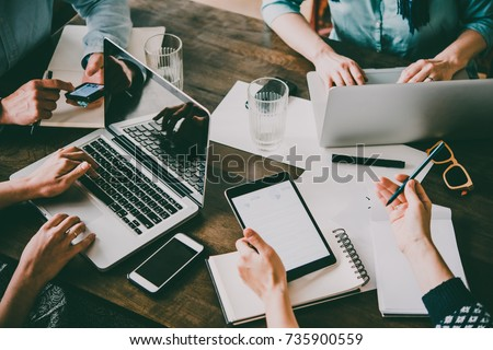 Laptop, mobile phone, tablet and documents on a working table in creative office. Successful teamwork and business startup concept. Toned image Royalty-Free Stock Photo #735900559