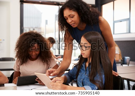 Teacher helping high school students with technology Royalty-Free Stock Photo #735905140