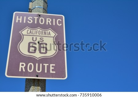 Historic California Route 66 road sign on a blue sky. #735910006