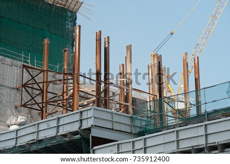 New hotel/tower building construction site on sunny day with clear blue sky in Hong Kong #735912400