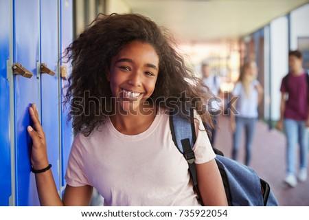 Portrait of black teenage girl by lockers in school corridor #735922054