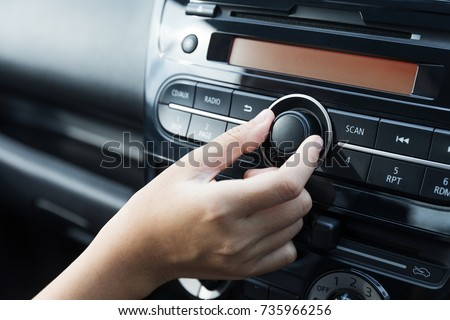 Women turning button on car radio for listening to music #735966256