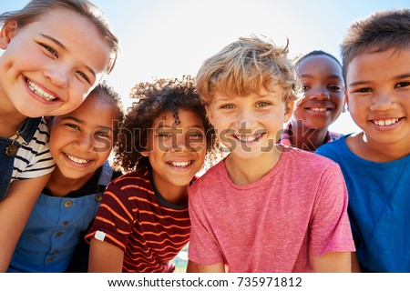 Close up of pre-teen friends in a park smiling to camera Royalty-Free Stock Photo #735971812