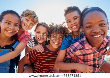 Six pre-teen friends piggybacking in a park, close up portrait