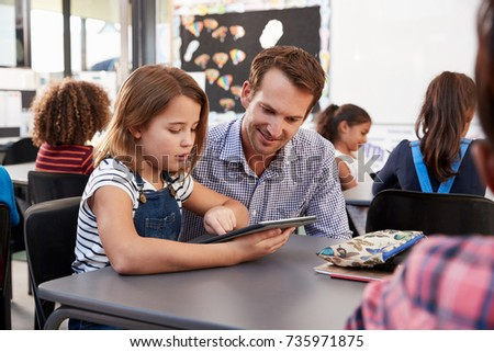 Teacher and young schoolgirl using tablet in classroom #735971875