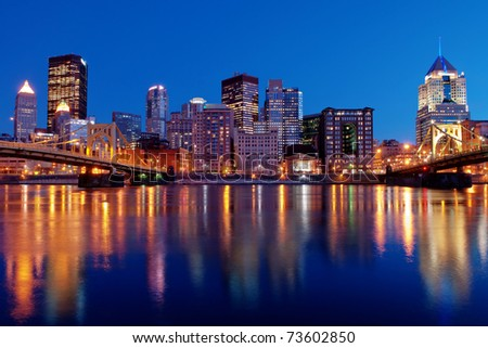 A view of the Pittsburgh, Pennsylvania cityscape at night overlooking the Allegheny River with views of the Roberto Clemente Bridge and Andy Warhol Bridge.