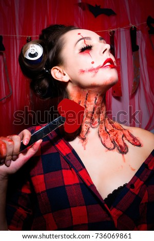 Woman posing holding cupid's arrow.Sad woman clown dressed in a Halloween costume.The concept of the high holidays.Sexy Woman with dripping blood.Halloween art design. Closeup girl clown.