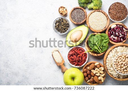 Superfoods on a gray background with copy space. Nuts, beans, greens and seeds. Healthy vegan food. #736087222