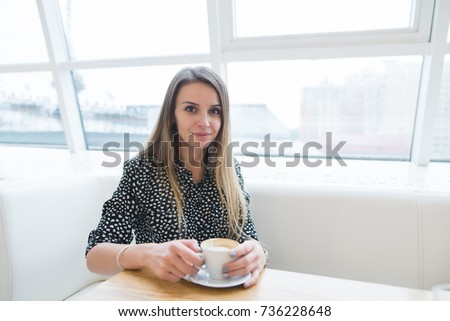 Beautiful woman sitting in a stylish light cafe near the window with a cup of coffee in her hands #736228648