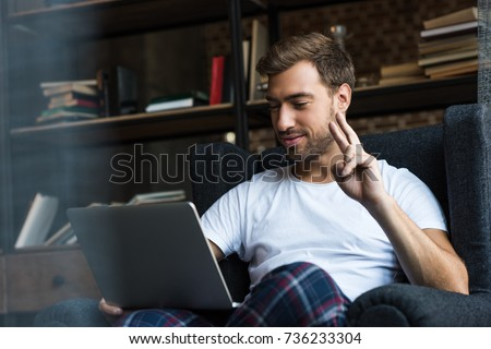 Young man sitting with laptop in armchair and showing a peace sign #736233304