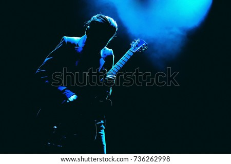 Guitarist silhouette in a dark on a stage in blue lights playing solo #736262998