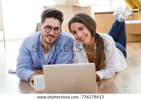 Portrait of beautiful young couple using laptop in their new home. #736278613
