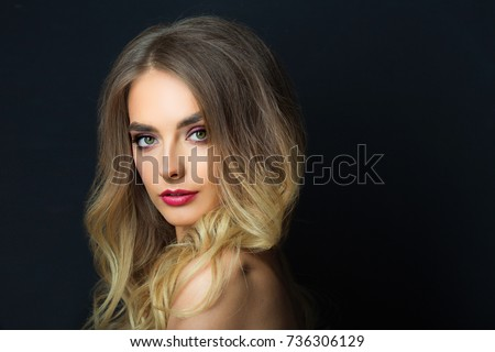 portrait of a beautiful young girl with makeup and hair-dress on a black background #736306129