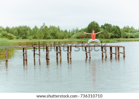A man doing yoga on wooden pier at the lake #736310710