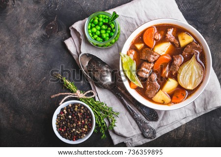 Meat stew with beef, potato, carrot, onion, spices. green peas. Slow cooked meat stew in bowl, wooden background. Hot autumn/winter dish. Closeup. Top view. Space for text. Comfort food. Homemade soup #736359895