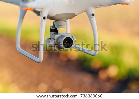 Close up on white drone camera. Drone quadcopter in flight #736360060