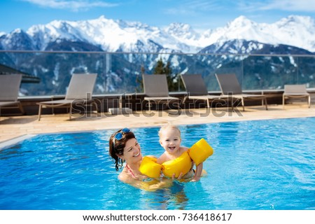 Mother and baby play in outdoor swimming pool of luxury spa alpine resort in Alps mountains, Austria. Winter and snow vacation for family with children. Kids in hot tub outdoors with mountain view.  #736418617