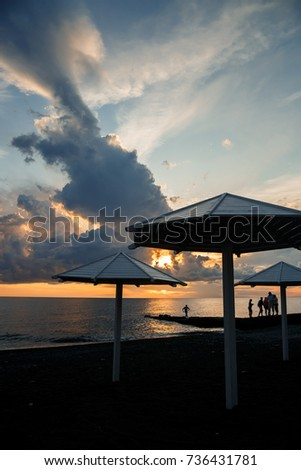 Beach umbrella at sunset, view of chairs and umbrellas on the beach. Sunset at the sea. beautiful sky on the beach. Wooden beach umbrella #736431781