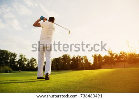 A man in a white suit made a great impact playing golf. He stands on a slit, well-groomed golf course and in his hands holds a golf club #736460491
