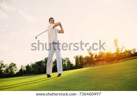 A man in a white suit is playing golf and just hit. He smiles, because the blow was excellent #736460497
