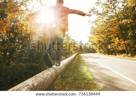 boy walking along the road fence. child keeps balance on the log. copy space for your text #736538449