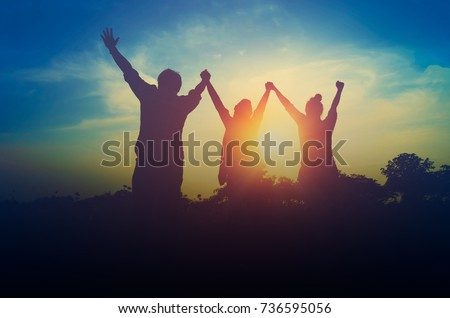 Silhouette of happiness teamwork hold hands up as a business successful, achieve business goal Royalty-Free Stock Photo #736595056