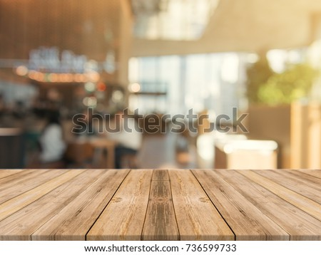 Wooden board empty table top on of blurred background. Perspective brown wood table over blur in coffee shop background - can be used mock up for montage products display or design key visual layout. #736599733