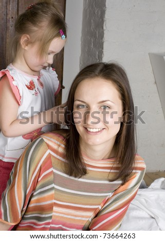 portrait of happy mother and daughter in bed, smiling hugging, holding green apple #73664263