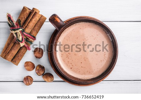 Hot cocoa with milk in brown clay cup, hazelnut and cinnamon sticks on table of white wooden planks, top view. #736652419