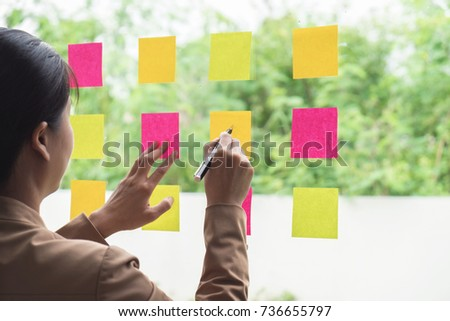 Young creative professional leader using post it notes in glass wall to writing strategy business plan, management and people concept. #736655797