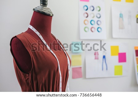 Red dummy with measuring tape in tailors studio, Creative Design and Artistic Concept.