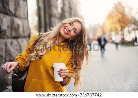 Stylish happy young woman wearing boyfriend jeans, white sneakers bright yellow sweatshirt.She holds coffee to go. portrait of smiling girl in sunglasses and bag #736737742