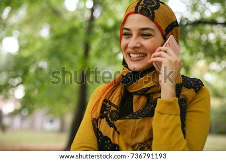 Young smiling Muslim woman using smart phone outdoor.  #736791193