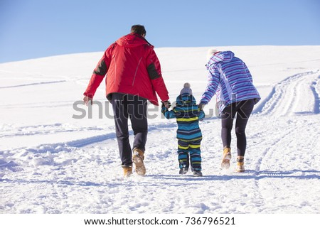 Attractive family having fun in a winter park on mountain #736796521
