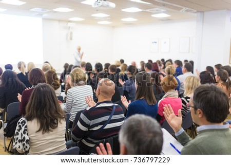 Life coaching symposium. Female speaker giving interactive motivational speech at entrepreneurship workshop. Audience in conference hall. Rear view of unrecognized participant. #736797229