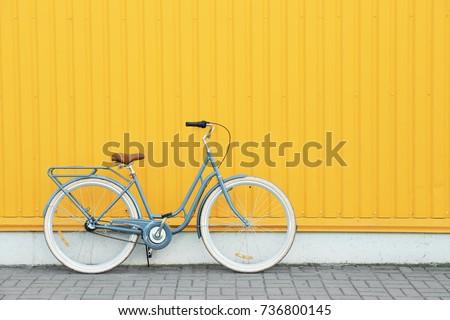 Retro bicycle near yellow wall outdoors Royalty-Free Stock Photo #736800145