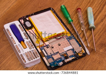 On a wooden table, the tablet is disassembled and screwdrivers for repair #736844881
