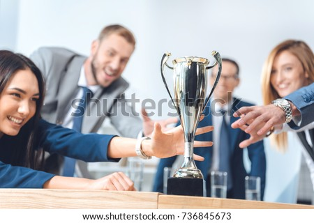 close-up shot of businesspeople trying to catch champion cup Royalty-Free Stock Photo #736845673