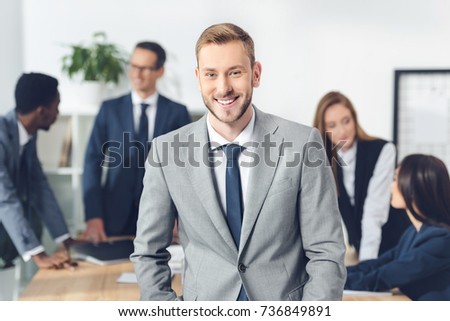 handsome young manager looking at camera with blurred businesspeople in conference hall #736849891