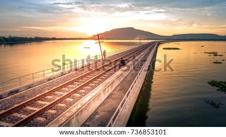 Couple tourist Taking pictures of sunset on Railroad Bridge Over Lake Khok Slung Pa Sak Dam Lopburi Thailand enjoying for view of nature during her him vacation #736853101