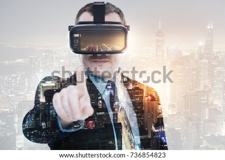 Pleasant businessman wearing VR headset and pointing at camera #736854823