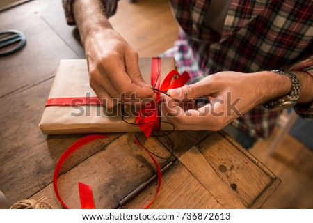 Young adult man with long blonde hair wrapping christmas present with red ribbon seated on wooden table in cozy apartment indoor. #736872613