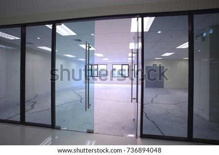 Interior empty office light room with white wallpaper without furniture in a new building renovation or under construction.Glass doors and Windows. #736894048