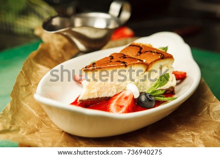 cheesecake on a white plate with strawberries #736940275