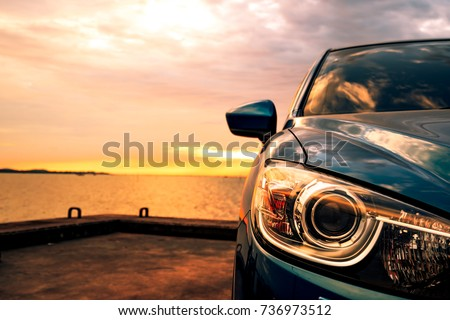 Blue compact SUV car with sport and modern design parked on concrete road by sea at sunset. Environmentally friendly technology. Hybrid and electric car technology. Car parking space. summer travel. #736973512